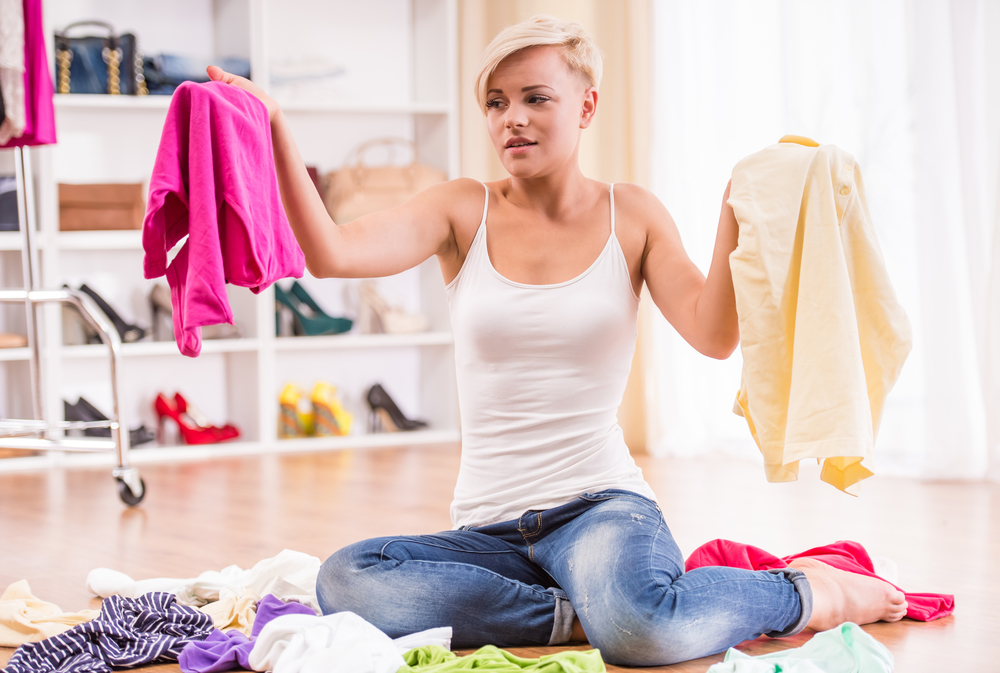 Young woman sitting on the floor trying to declutter her clothes.